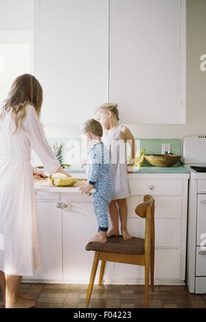 Woman standing in a kitchen, cutting a fresh pineapple for her children. - Stock Photo