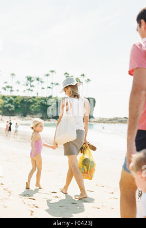 Family on a day out at a sandy beach by the ocean. - Stock Photo