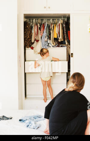 Young girl looking for clothes in a chest of drawers, her mother sitting on a bed, watching. - Stock Photo