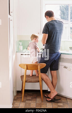 Man standing in a kitchen, his son standing on a chair beside him. - Stock Photo