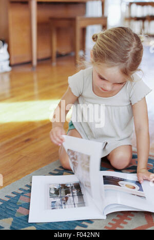 Young girl sitting on the floor, reading a lifestyle magazine. - Stock Photo