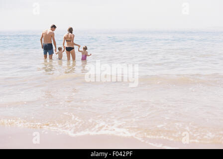 Couple with their son and daughter, A family standing in shallow water off the beach. - Stock Photo