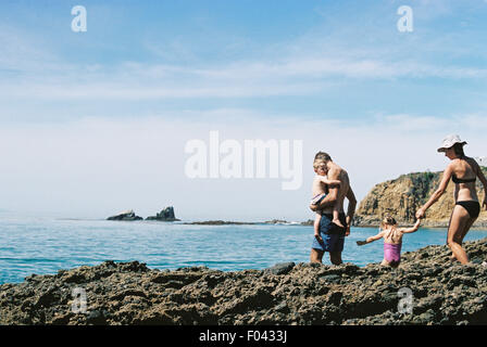 A family on holiday, two adults with their son and daughter walking across rocks by the ocean. - Stock Photo