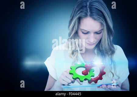 Composite image of woman using tablet pc - Stock Photo
