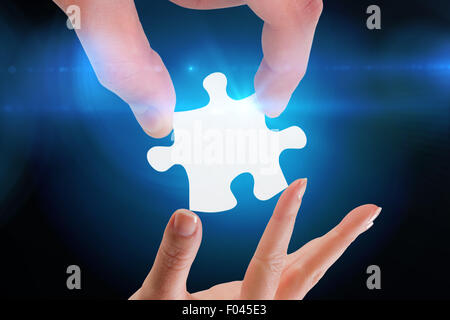Composite image of hands holding jigsaw - Stock Photo