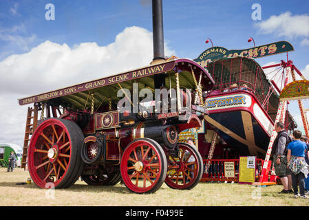 Showmans Traction Engine and fairground ride at a steam fair in England - Stock Photo