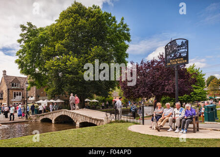 Tourists enjoy summer afternoon in the Cotswold village of Bourton-on-the-Water, Gloucestershire, England. - Stock Photo
