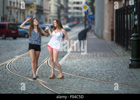 Funny teen girls together walking on the pavement on the street. - Stock Photo