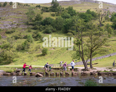 Family crossing the stepping stones over the river Dove in Dovedale, Derbyshire Peak District, England, UK - Stock Photo