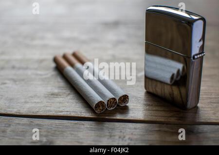 Cigarettes with Reflective Silver Zippo - Stock Photo