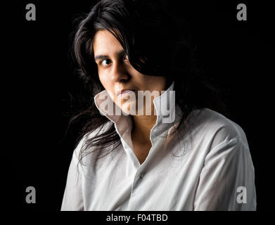 Latina teen in white shirt standing in front of black backdrop and looking at the camera - Stock Photo