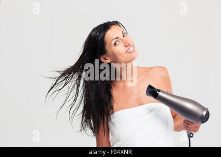 Pretty young woman in towel drying her hair isolated on a white background - Stock Photo