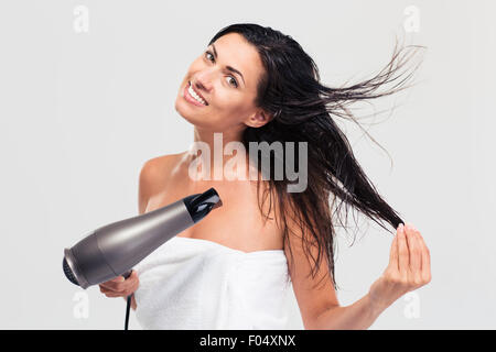 Smiling cute woman in towel drying her hair isolated on a white background - Stock Photo
