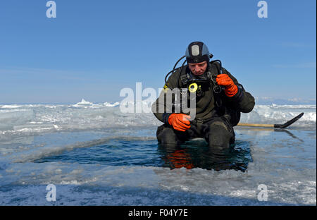 Ice diver by an ice hole preparing to dive, checking his equipment, lake Baikal, Siberia, Russia - Stock Photo