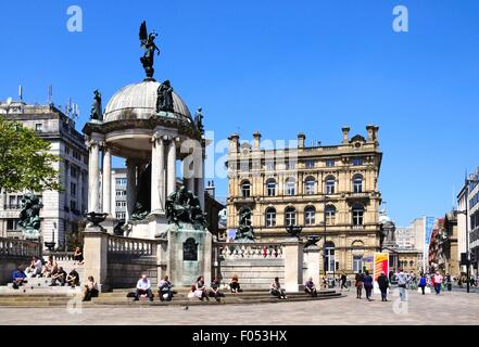 The Queen Victoria monument in Derby Square with tourists sitting on the steps enjoying the Summer sunshine, Liverpool, - Stock Photo