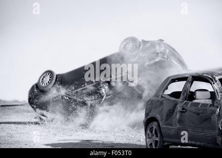 two cars turned upside-down after road collision, monochromatic - Stock Photo