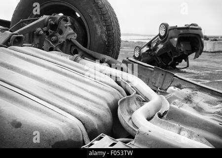 two cars turned upside-down after road collision. Monochromatic - Stock Photo