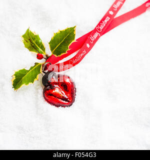 heart shaped red bauble with holly and Merry Christmas ribbon on snow - Stock Photo