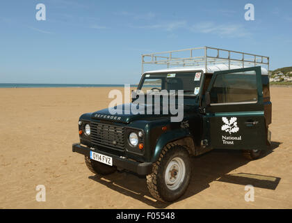 National Trust Rangers Land Rover Defender on Woolacombe Beach North Devon - Stock Photo