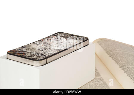 A broken smartphone on white background. The smartphone has a badly damaged screen with spiderweb cracks, and its - Stock Photo
