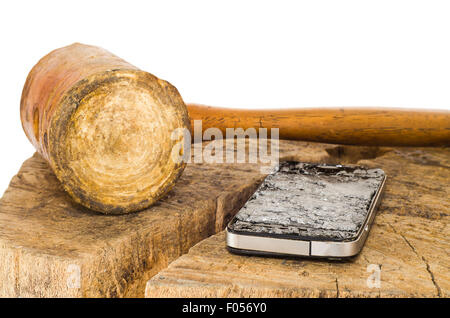 A broken smartphone and leather hammer on white background.. The smartphone has a badly damaged screen with spiderweb - Stock Photo
