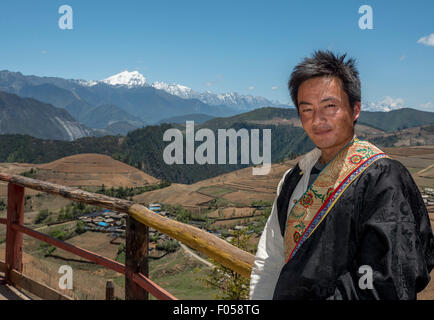 A Tibetan Man Dressed In Traditional Costume Poses In Front Of Meili Snow Mountain In Yunnan Province China - Stock Photo