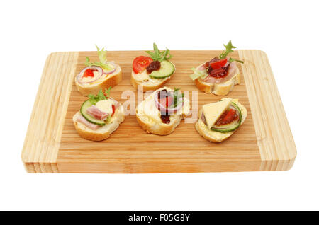 Selection on canapes on a wooden board isolated against white - Stock Photo