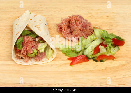Pulled pork bread wrap with ingredients on a wooden board - Stock Photo