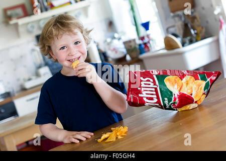 Young boy, 4 years, eating crisps - Stock Photo