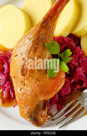 Dish of roast duck leg with potato dumplings and braised red cabbage - Stock Photo