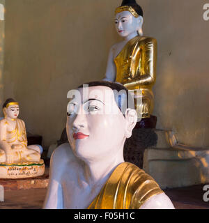 Buddha statues at Shwedagon Paya in Yangon, Myanmar. Foreground figure with atypical slanted shoulder pose and expressive - Stock Photo
