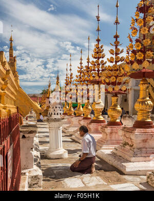 Men kneeling to pray in front of main stupa of Shwedigon paya in Nyaung U Myanmar near Bagan - Stock Photo