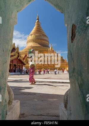 Woman carrying basket on her head walks across plaza in front of Shwezigon Pagoda stupa in Nyaung U Myanmar. View - Stock Photo