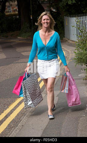 Woman walking in the street carrying paper recyclable carrier shopping bags - Stock Photo