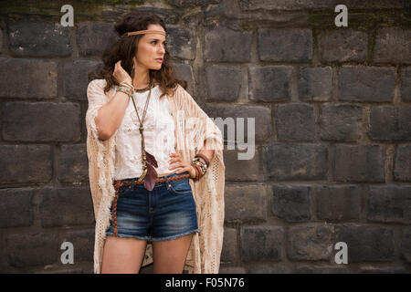 Longhaired hippy-looking young lady in jeans shorts, knitted shawl and white blouse stands near stone wall in old - Stock Photo