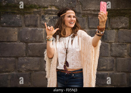 Longhaired hippy-looking young lady in jeans shorts, knitted shawl and white blouse standing near stone wall in - Stock Photo