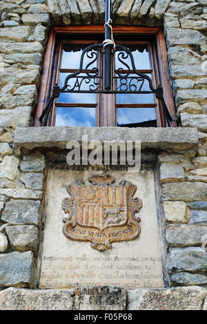 Andorra's coat of arms on the brick wall of the General Council of Andorra. - Stock Photo