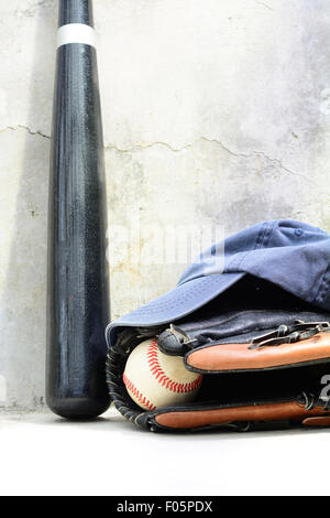 Baseball bat wit a cap and a glove with a ball in it - Stock Photo