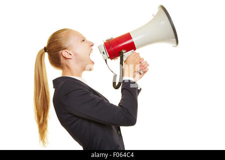Young blonde businesswoman screaming loudly into a megaphone - Stock Photo