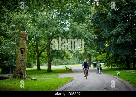 A cyclist passing the large tree carving in memory of the animals that died, Woodbank Memorial Park in Offerton, - Stock Photo