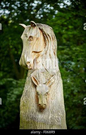 Woodbank Memorial Park in Offerton, Stockport, UK.   A cyclist passing the large tree carving in memory of the animals - Stock Photo