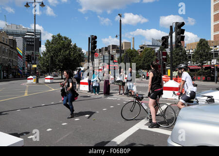 A female cyclist waits at traffic lights for a pedestrian on a street crossing in Old Street,  East London  UK  - Stock Photo