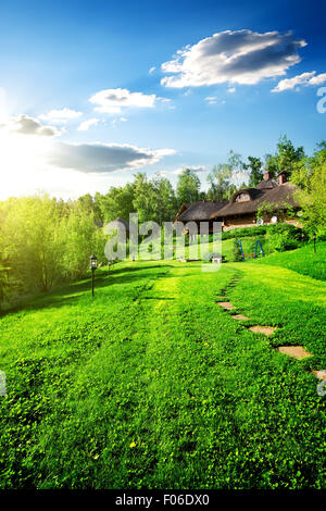 Wooden houses on green meadow in spring - Stock Photo