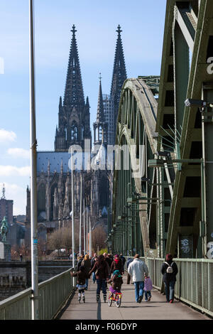Pedestrian walking along the Hohenzollern Bridge with the Cologne Cathedral,  Kölner Dom, behind - Stock Photo