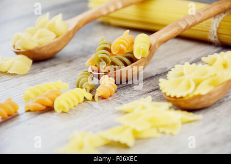 Three kinds of raw pasta in wooden spoons on the table - Stock Photo