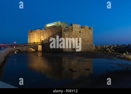 Illuminated Paphos Castle located in the city harbor at night with reflection in the water, Cyprus - Stock Photo