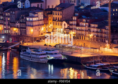Porto in Portugal by night, houses and cruise boats along Douro river waterfront in historic city centre. - Stock Photo