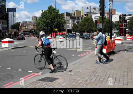A woman pushes off from the curb on a bicycle in Old Street East London  UK  KATHY DEWITT - Stock Photo
