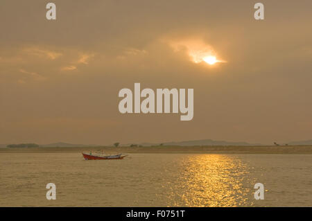 ASIA, MYANMAR (BURMA), Bagan, Irrawaddy River, ferry boat on river as sun sets - Stock Photo