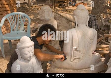 ASIA, MYANMAR (BURMA), Mandalay, young man sanding down a statue of Buddha in outdoor factory - Stock Photo